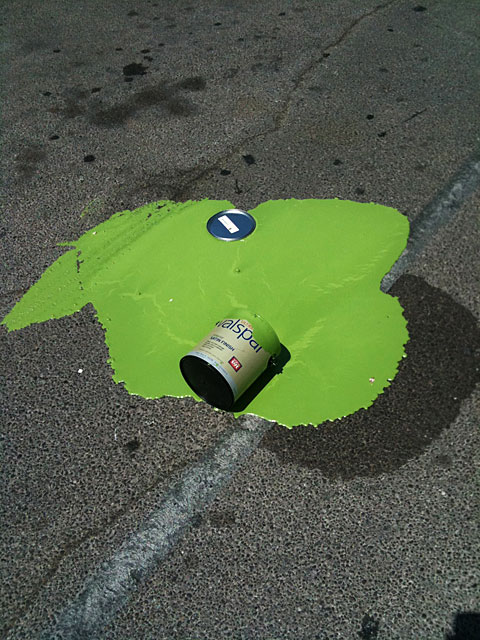 Photo of a can of green paint spilled in a parking lot