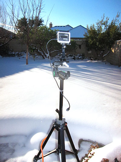 GoPro camera mounted on tripod in front of snow-covered yard