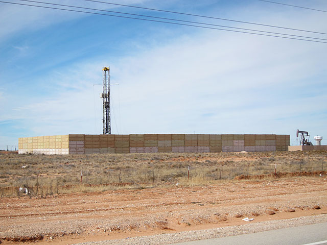 Photo of sound barrier in front of drilling rig