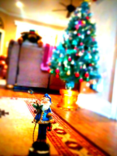 Photo of toy Santa against lit Christmas tree