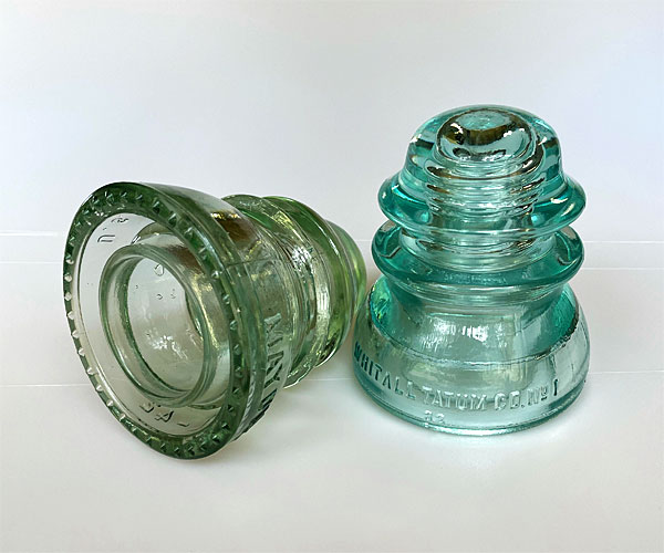 Photo - Two glass insulators, one pale green and one smoky clear color
